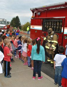 A volunteer firefighter in front of a fire truck speaks to a group of elementary students about fire safety.