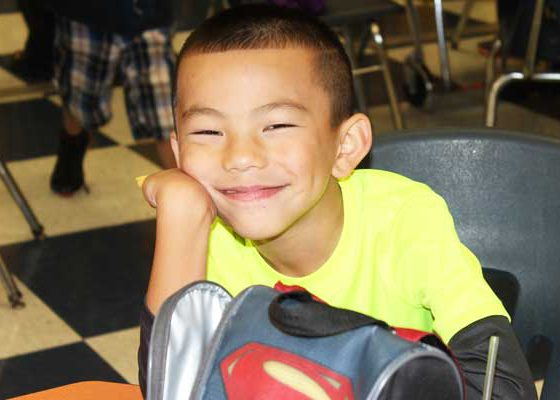A smiling elementary boy at a lunch table