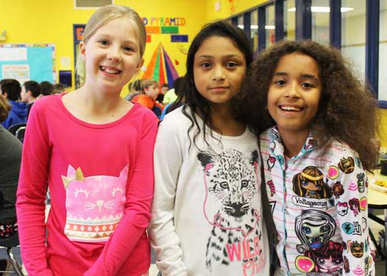 Three elementary girls smile for a portrait