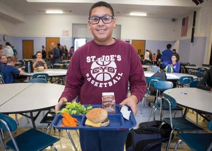 A male students in a basketball shirt carries a full lunch tray in the high school cafeteria