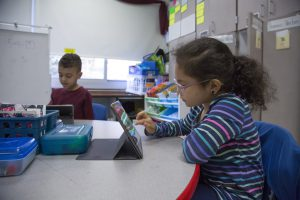 An elementary girl in her classroom works on a chromebook