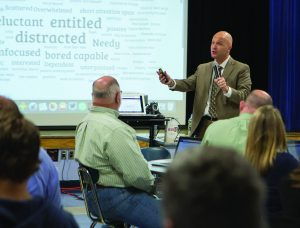 Eric Sheninger, in front of a projection screen, gives his presentation to a cafeteria filled with teachers.