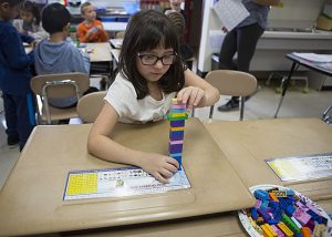 A female student wearing glasses is seated working with a lego structure