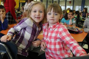 Two elementary girls in plaid at a cafeteria table.