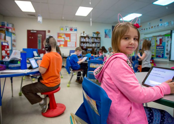An elementary girl in pink any bunny ears works on a tablet