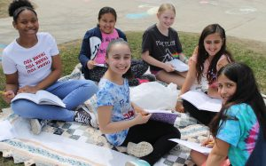 Six female elementary students on a picnic blanket reading outside