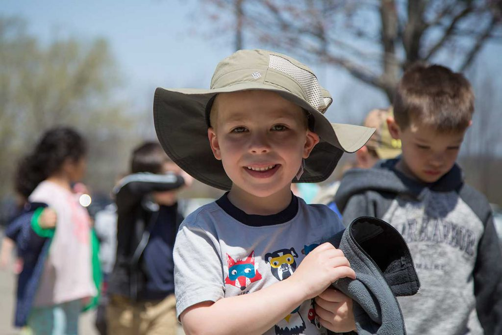 A pre-k boy in a floppy fishing hat in the sunshine