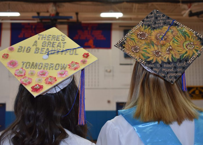 Two graduation caps decorated with flowers on female graduates
