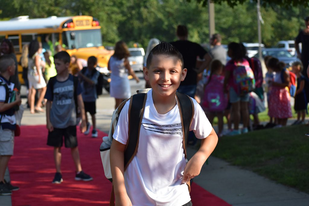 An elementary boy in a white shirt heads into school