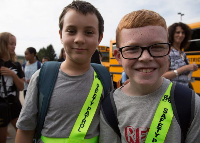 A portrait of two elementary boys, one wearing glasses, and both wearing yellow safety patrol sashes