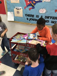 a student selects a book from a  book cart