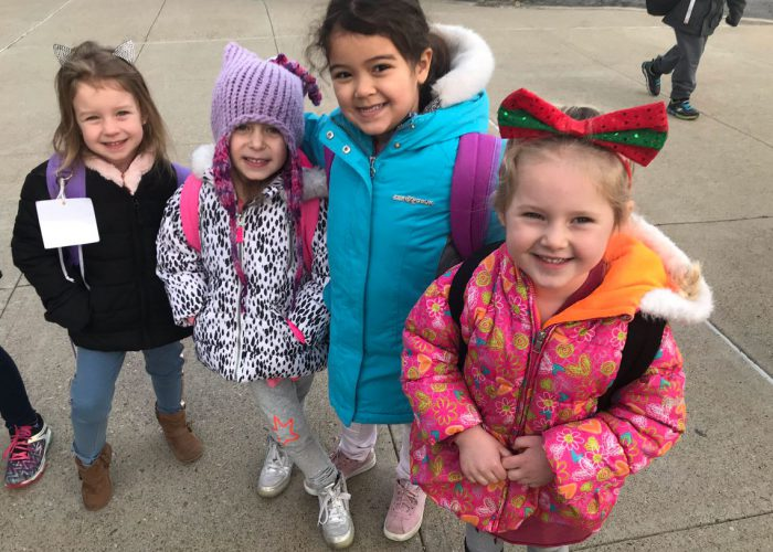 Four elementary girls in winter coats smile and head into school