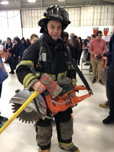 A students wears firefighter gear