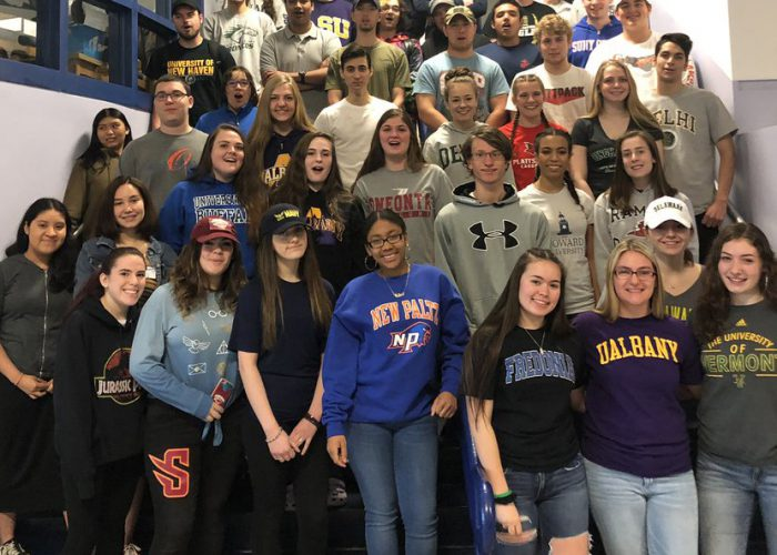 A group photo of about 40 seniors on a staircase, all wearing college t-shirts or hats