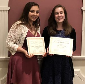Two high school girls hold certificates