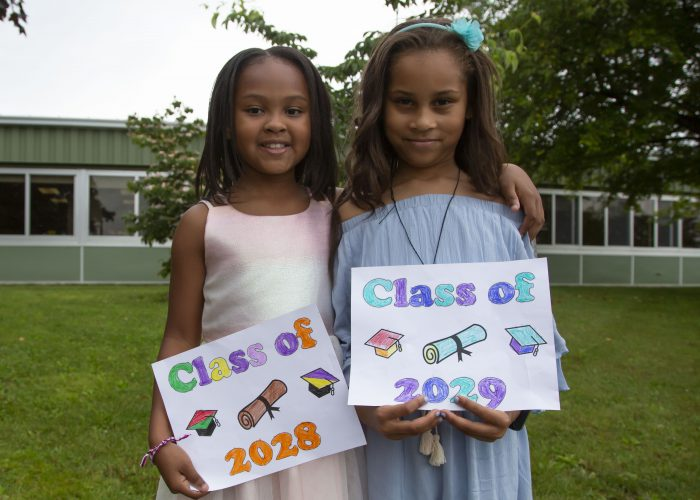 Two elementary girls hold Class of 2028 and 2029 signs
