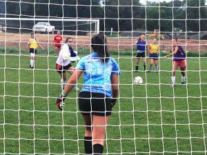 Girls soccer athletes playing in field seen through goal net