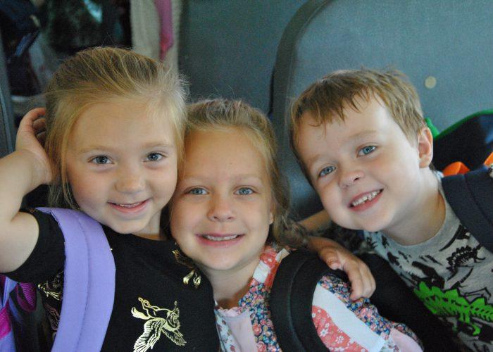 three students on a school bus