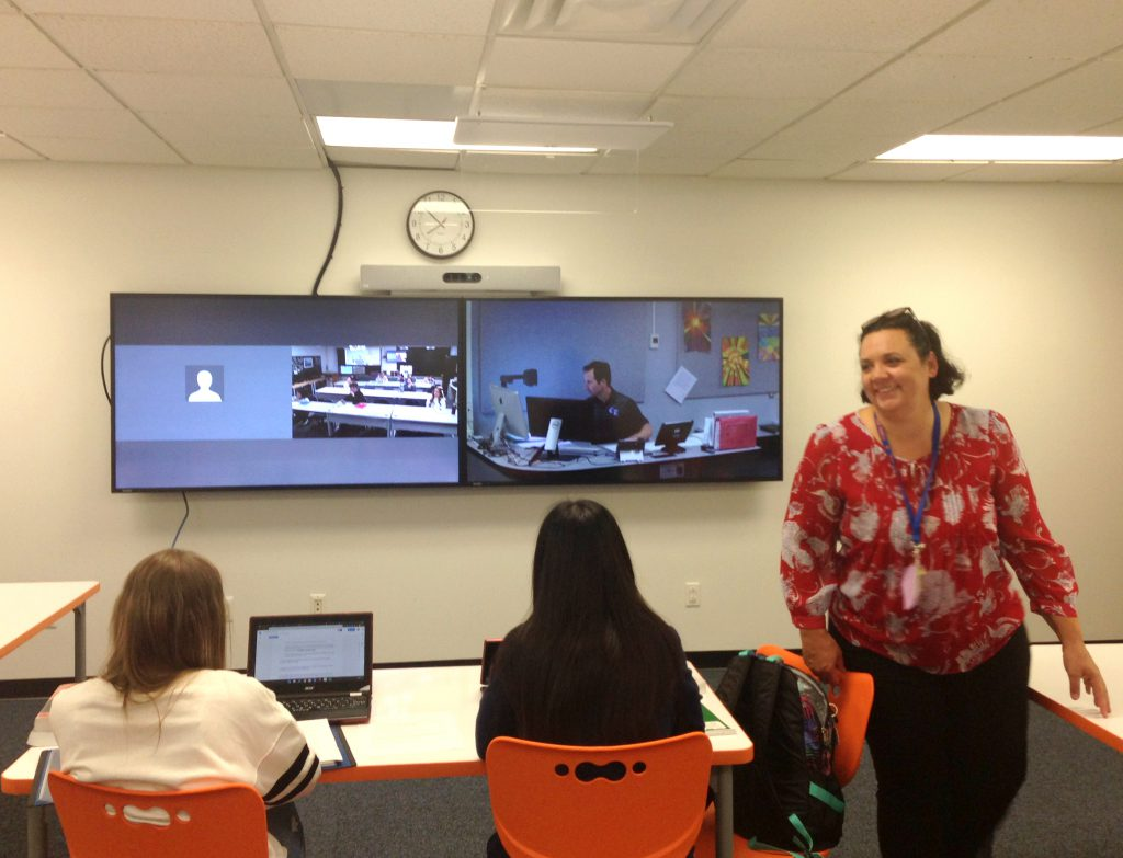 Two students sit in a classroom facing two smart board screens videoing in a distance learning course. A teacher aide walks past the students facing the camera.