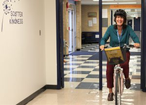 "Sschool principal riding a bicycle in a school hallway. The bike as a basket with a children's book title ""The Lion Inside"""