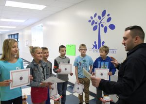 Firefighter stands in school hallway with group of students handing them award certificates.