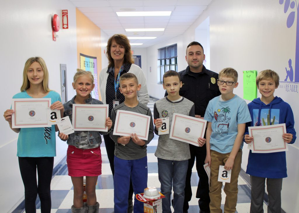 A group of students pose holding their award certificates. They are joined by their school principal and the firefighter who presented the awards.