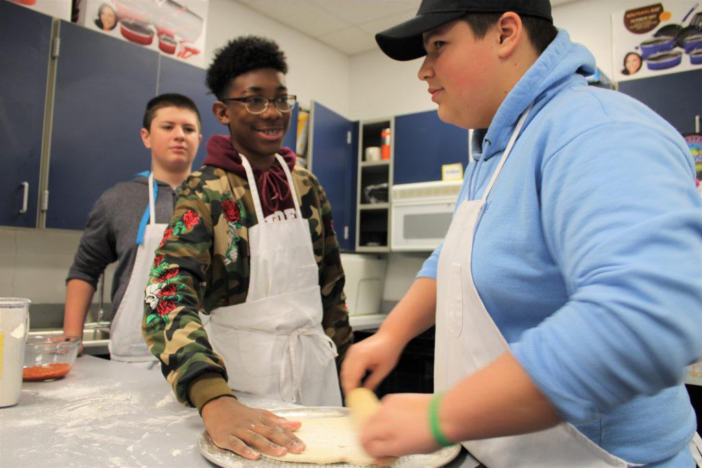 Students rolling pizza doug