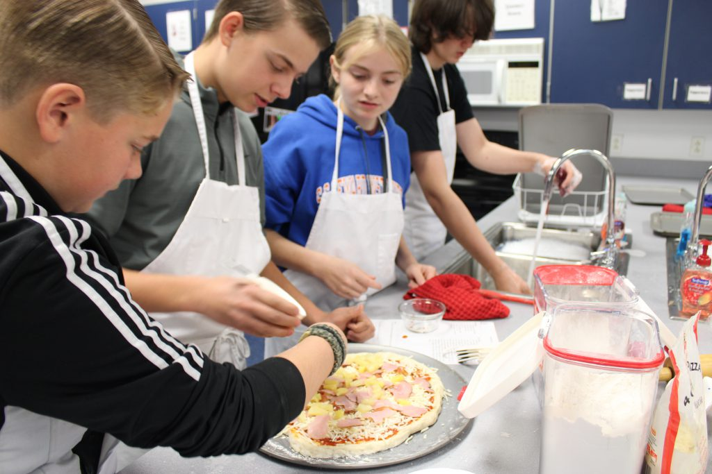 Students adding ingredients to pizza dough
