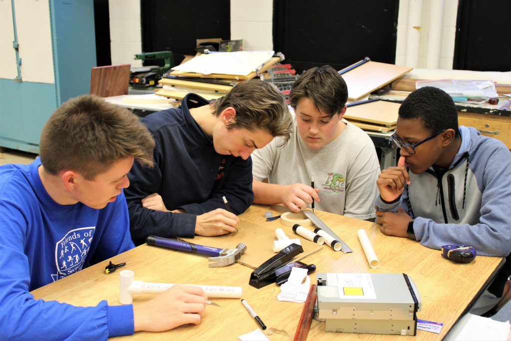 Four students work at a table in technology class