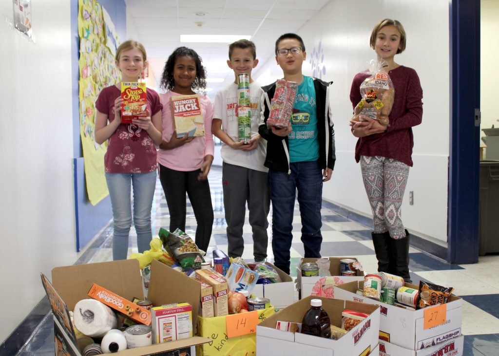 Five students posing with food items in front of a collection of boxes filled with food donations.