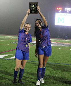 Two soccer players on a turf field hold a section win plaque
