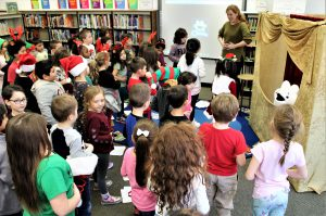 Puppet show presenter in the school library shows students how to take a deep, belly breath.