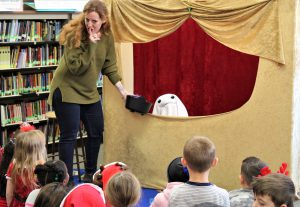 Adult presenter holds a plastic coup cauldron in front of a puppet ghost. She faces a group of students in the school library watching the show and signals them to keep quiet.