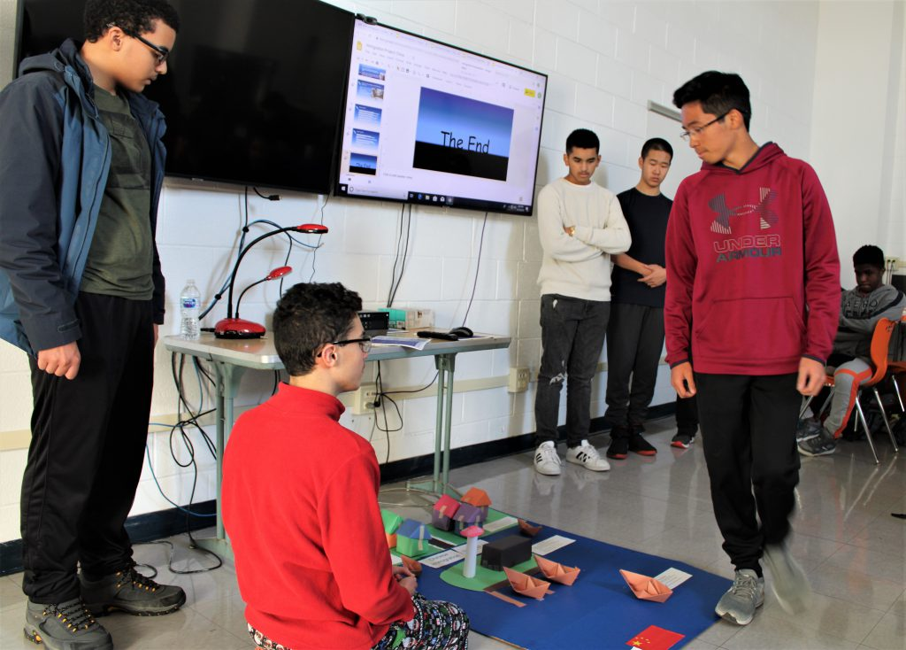 Presenting their project on early Chinese immigration to the U.S., two students stand by a smart board and three others gather around a mock-up of a Chinese fishermen village.