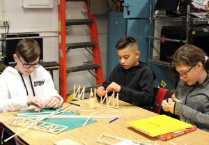 Three students are building a bridge-like structure out of balsa wood.