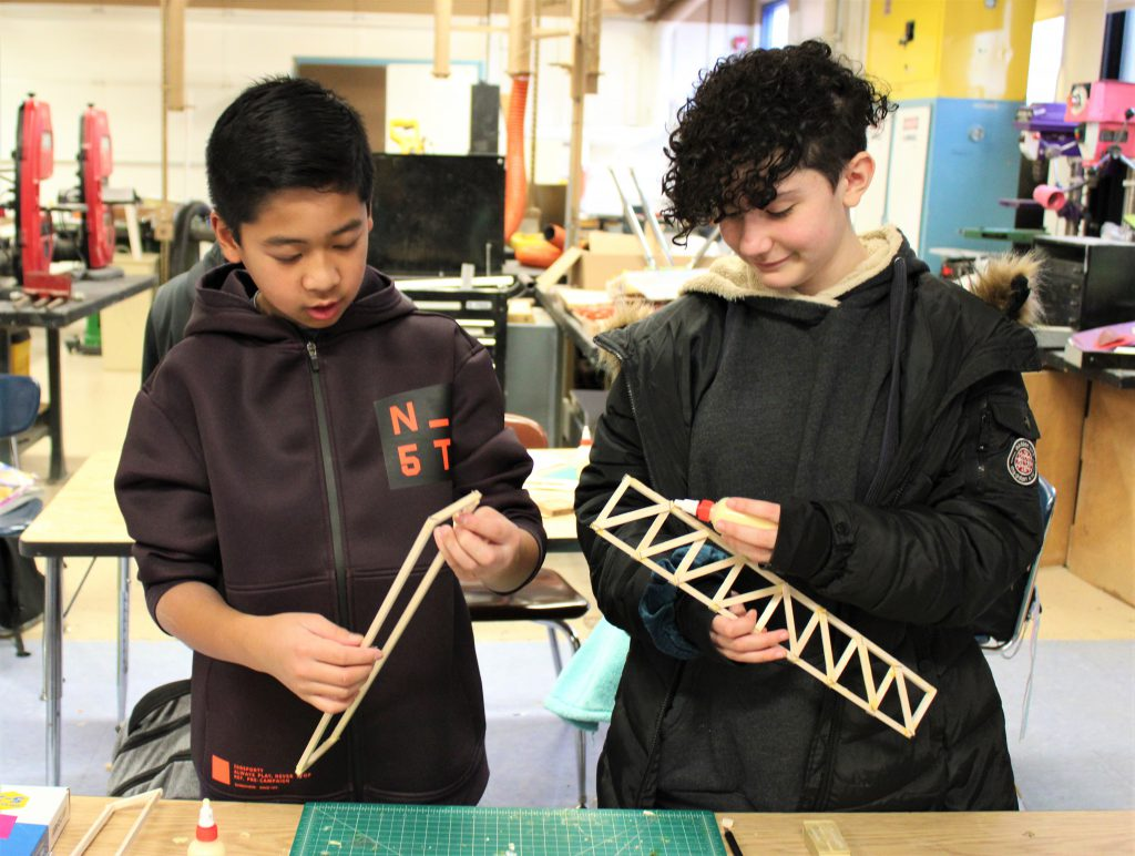 Two students are building a bridge-like structure out of balsa wood.
