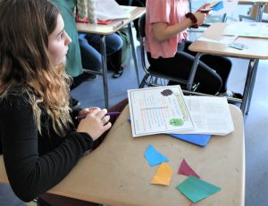 A student looks away from her desk where there are four paper polygons and a list.