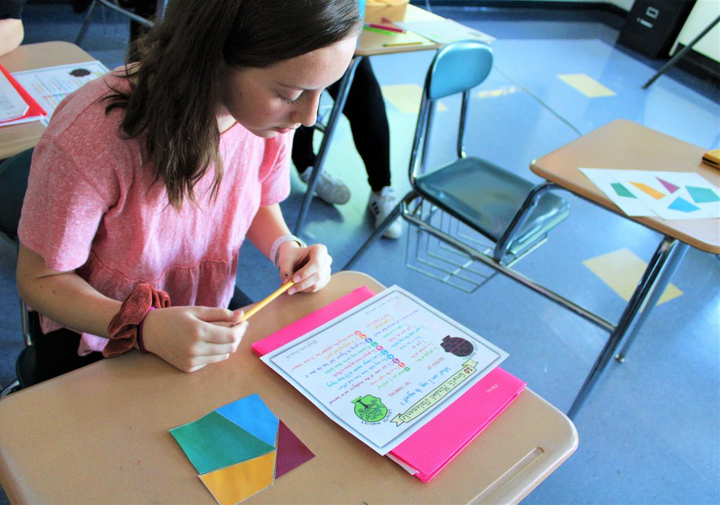 A student holding a pencil reads from a list on her desk. A square made of four, colorful sit next to the list. paper polygons