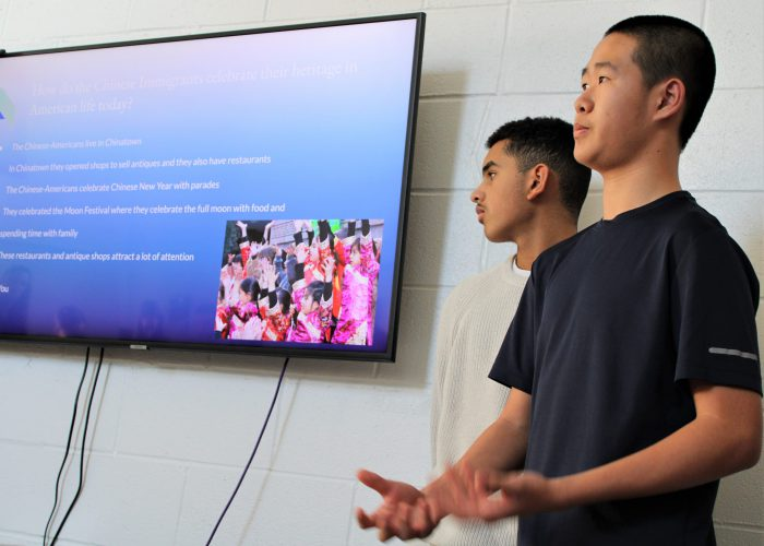 Two students use the smart board during a presentation