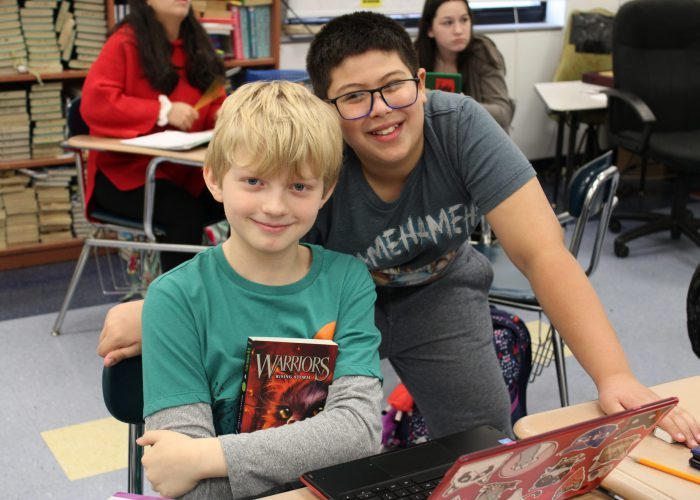 "Two students pose for a photo. One holds a book titled, ""Warriors."""