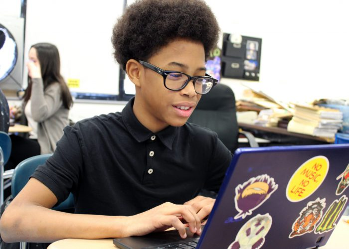 student at his laptop smiling