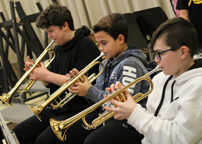 Three students playing trumpets