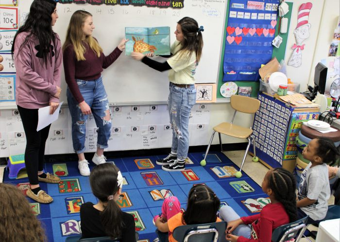 Three high school students read to a K class