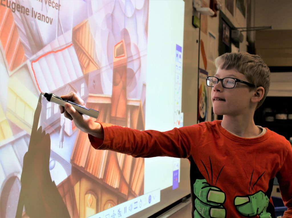 Student standing at a smart board uses a marker to trace polygons over a cubist painting of a cityscape.
