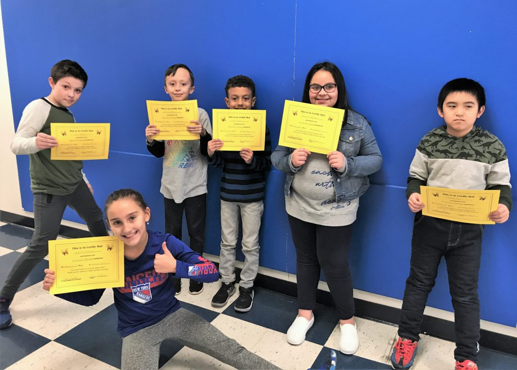 Group of students holding their spelling bee certificates
