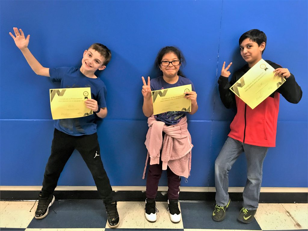 "Three students holding their spelling bee certificates and celebrating with ""V"" hand signs"