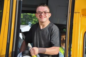 Student getting off of school bus smiles directly at camera