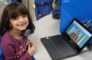 student working at a chromebook pauses for a big smile. The tooth fairy has visited recently.