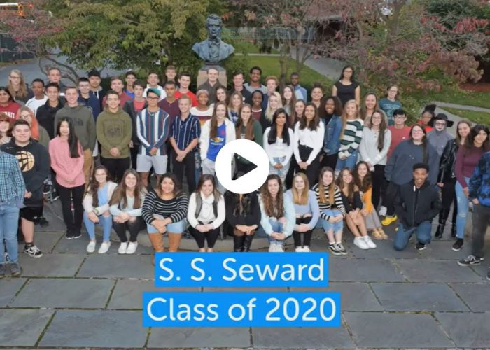 Image of the cover slide of a video slide presentation of the Class of 2020 recognition awards and scholarships. It shows the class posing in front to SS Seward's memorial.