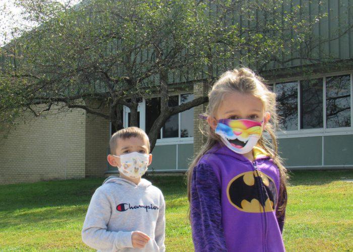 Two elementary kids a boy in a gray sweatshirt and a girl wearing a purple batgirl sweatshirt wear masks. A tree is in the background.